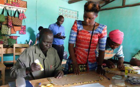 南スーダンからの来訪者にブックカバー作りを指導するウムチョ・ニャンザのアルフォンシンさん